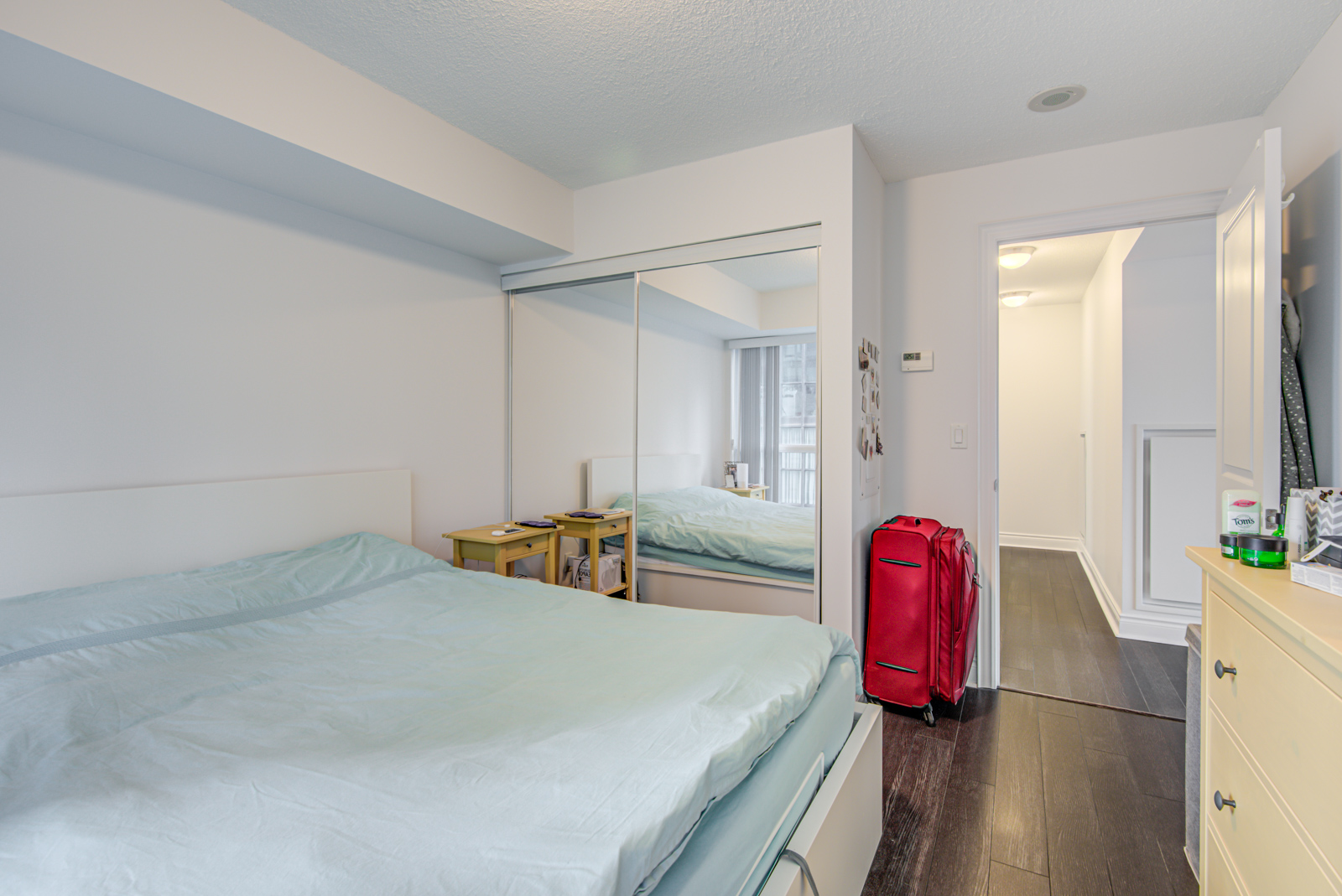 Bedroom with large white bed, sleek dark brown floors, red luggage bag, and closet with mirror doors.