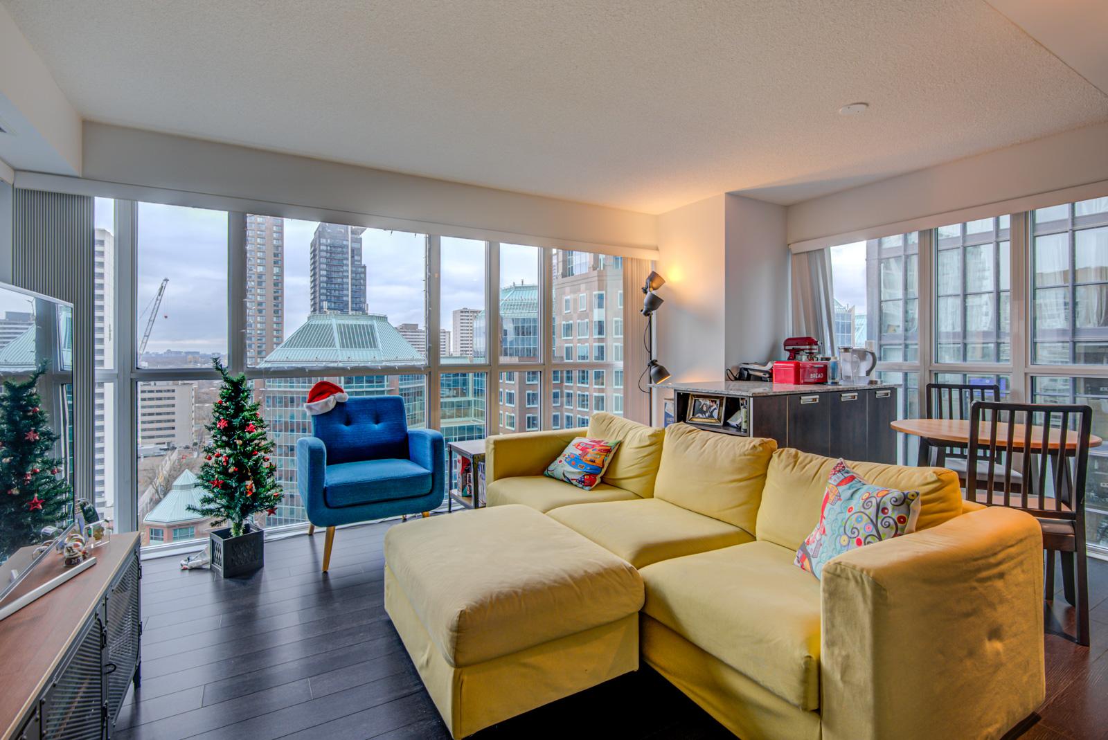 Living room with yellow sofa, blue armchair, sleek and dark laminate floors, and huge windows.