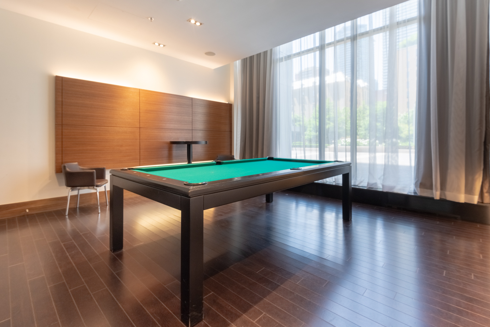 Empty room with large billiards table with green surface and dark brown floors at The Couture.