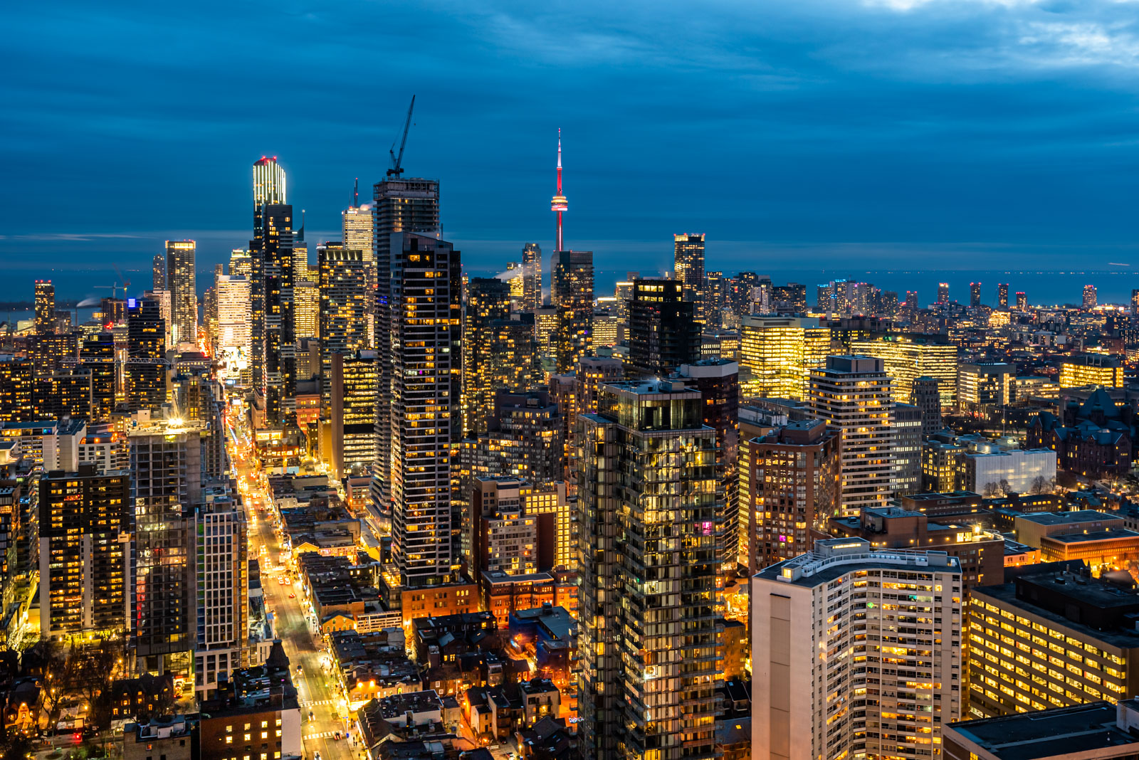 Aerial view of Toronto skyline at night with bright city lights and streets.