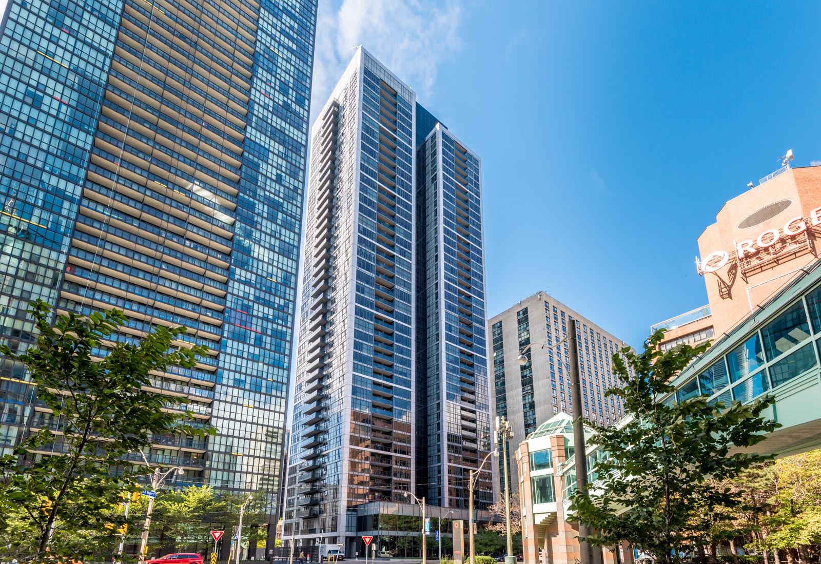 Daytime across-the-street view of The Couture Condos, a 42-floor building with highly-reflective glass.