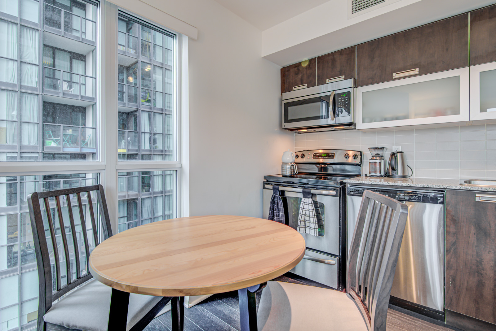 Kitchen with round dining table, stainless-steel stove, microwave, dishwasher and wooden cabinets.