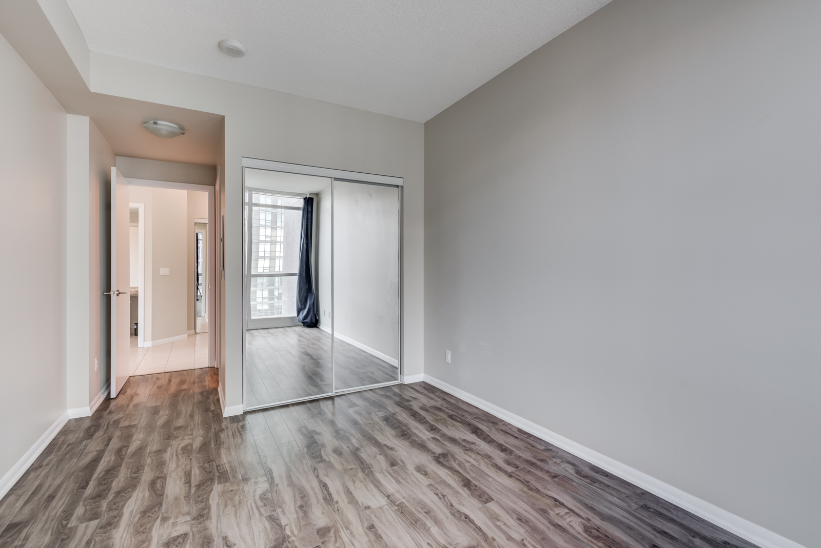 Empty master bedroom with dark brown laminate floors and closet with mirror doors.