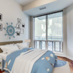 3D render of 300 Bloor St E Unit 1809 second bedroom with nautical theme featuring ship's wheel and blue bed-sheets.