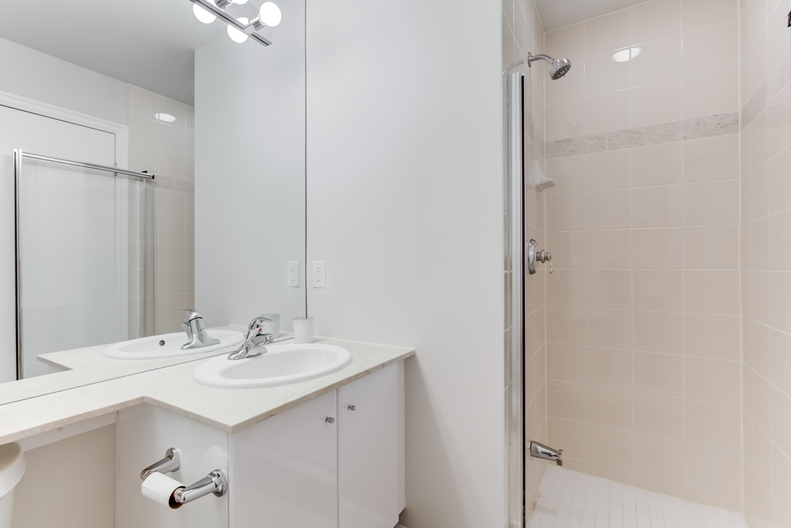Small bathroom with walk-in shower, chrome fixtures, beige tiles and white counter-tops.
