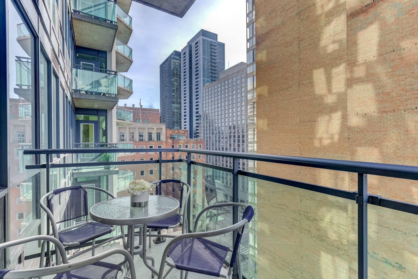 300 Bloor St E Unit 1809 balcony with round table surrounded by 4 chairs overlooking buildings along Rosedale Valley.
