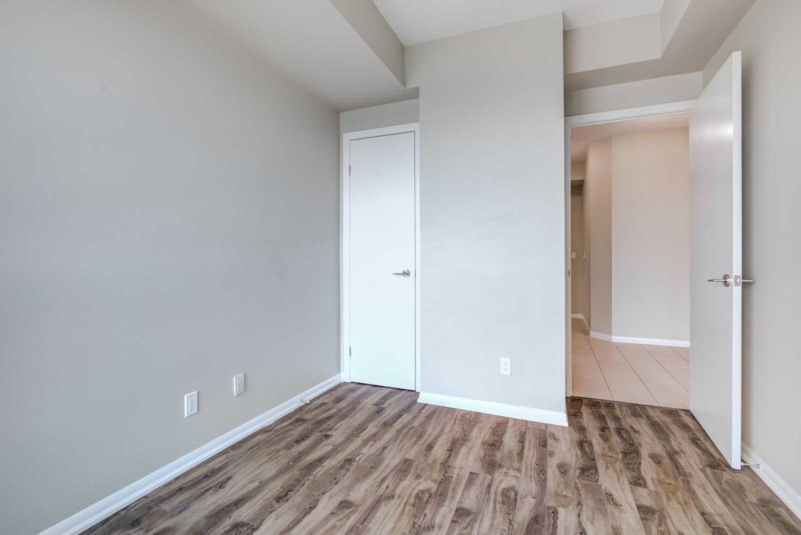 Empty bedroom with dark laminate floors, gray walls and white closet door.