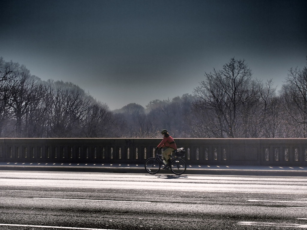 Female cyclist on bridge with snow-covered trees in background in Rosedale, Toronto.