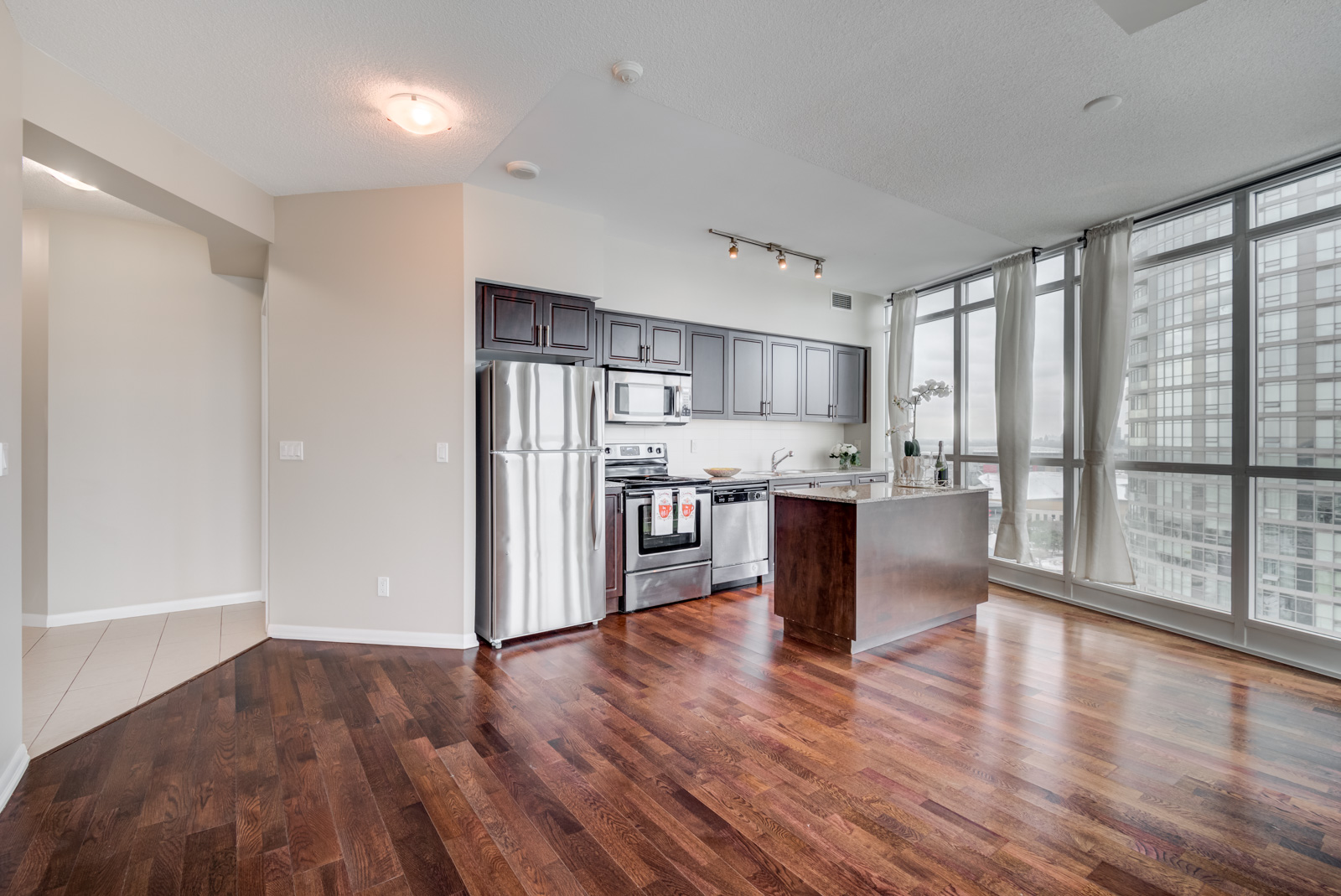 Shot of 215 Fort York Blvd Unit 2310 open-concept living and dining room with dark hardwood floors.