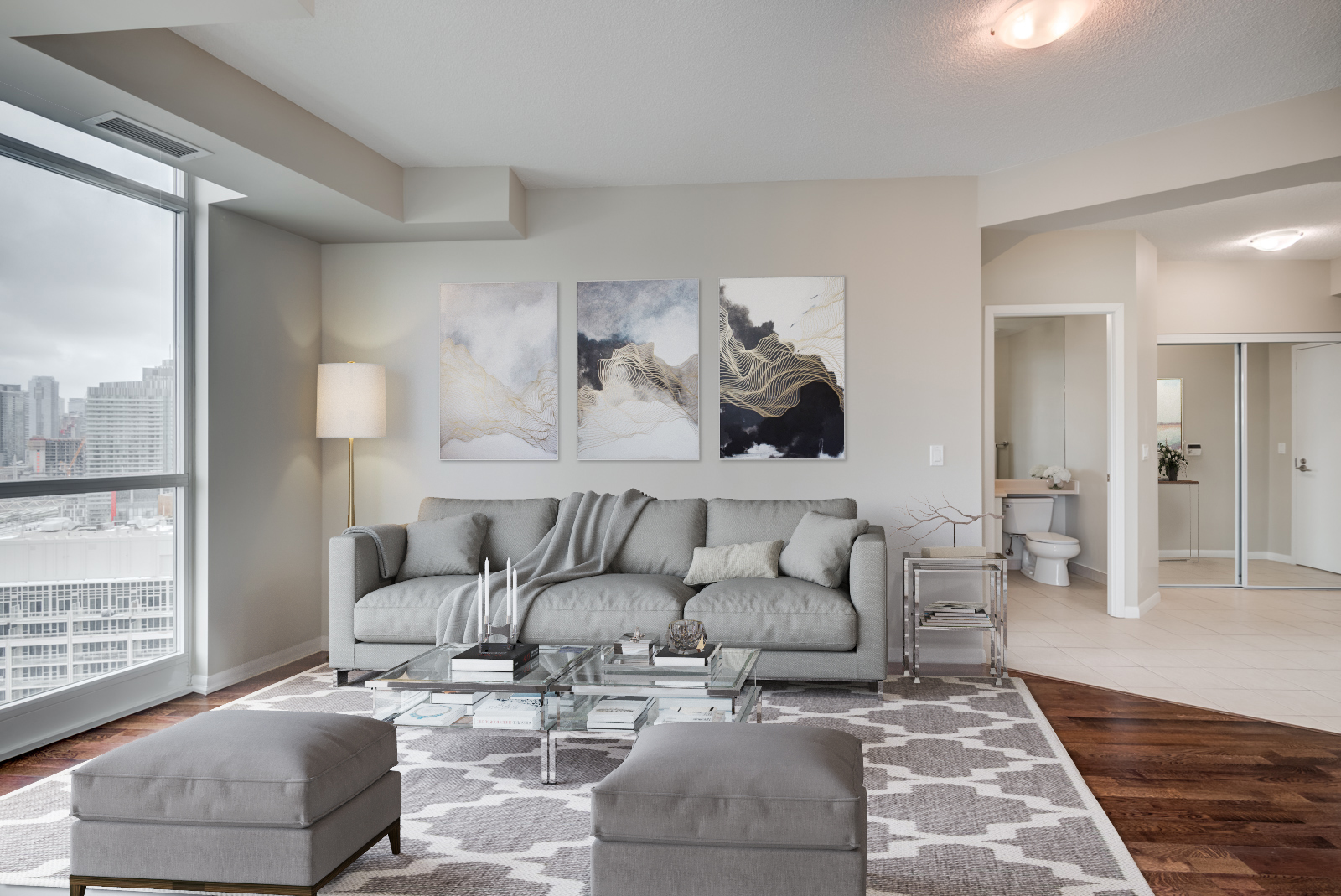 3D render of 215 Fort York Blvd living room with gray sofa, 2 ottomans, diamond-pattern rug and paintings.