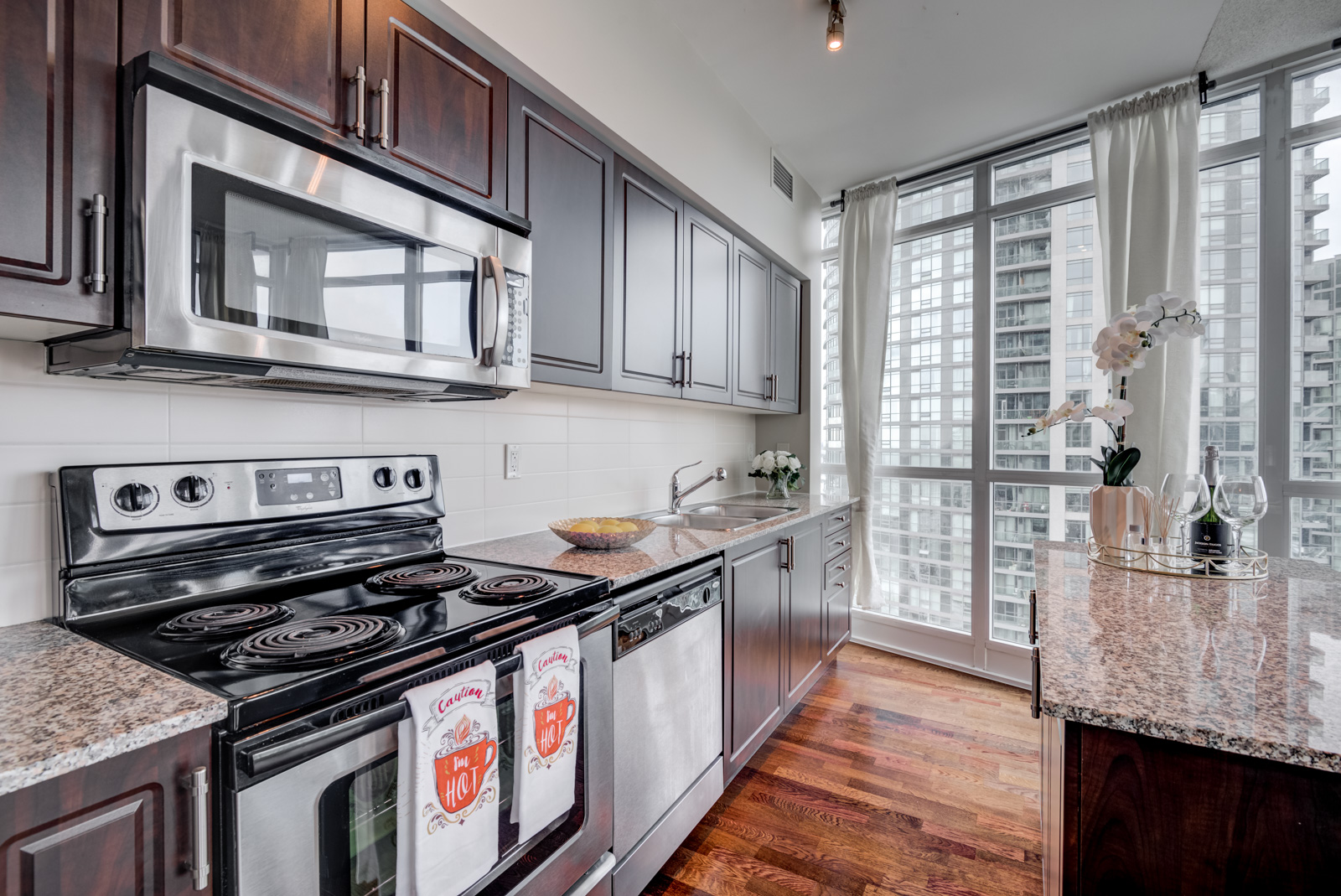 Linear kitchen and stainless oven, dishwasher and microwave at 215 Fort York Blvd Unit 2310.