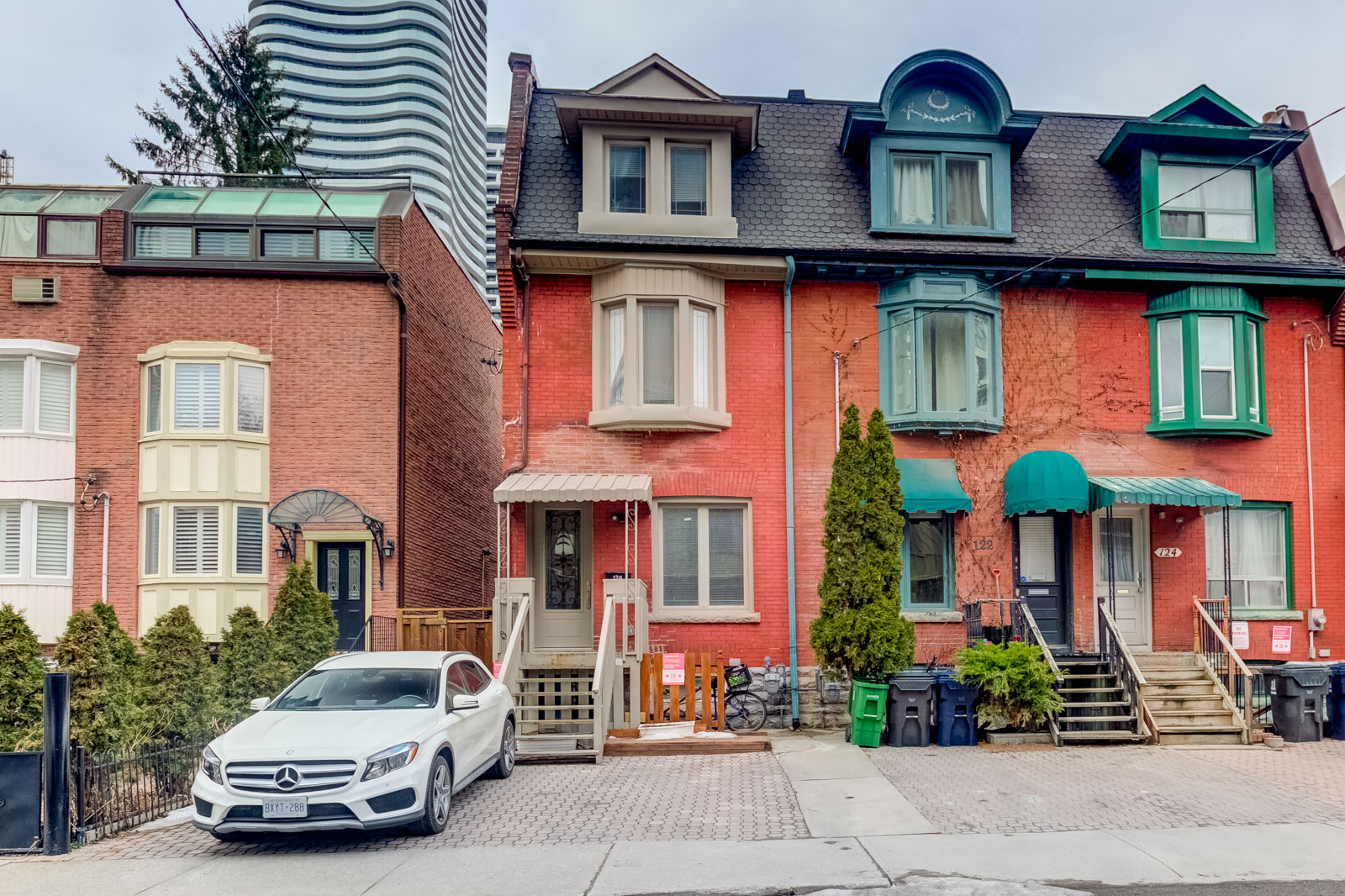3-storey red-brick Victorian house with white Mercedes Benz in driveway of 120 McGill St, Toronto.