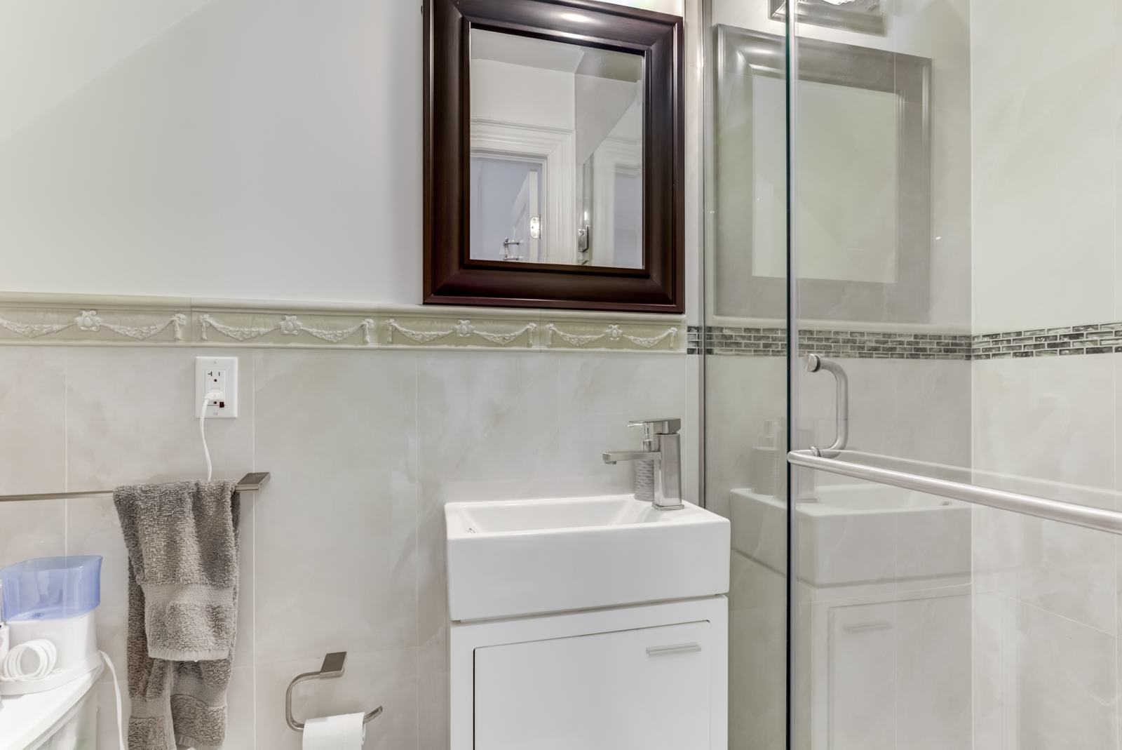Small washroom with glass walk-in shower, square sink and white walls.