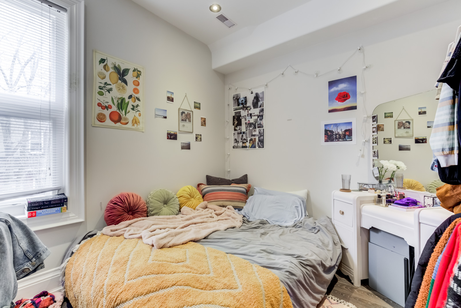 Messy bedroom with bed on floor, colourful sheets and pictures on wall.