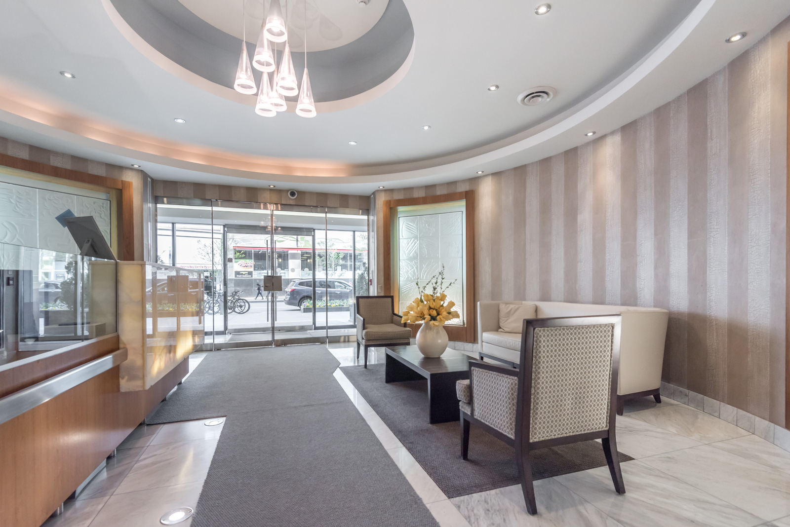 Elegant lobby and concierge desk of 85 Bloor Condos in Toronto.