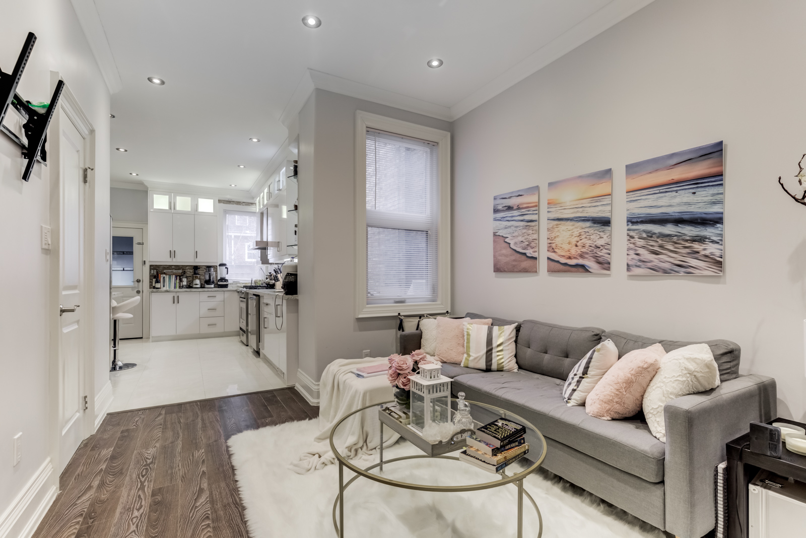 Renovated living room with gray sofa, thick white rug and gray walls hung with paintings.
