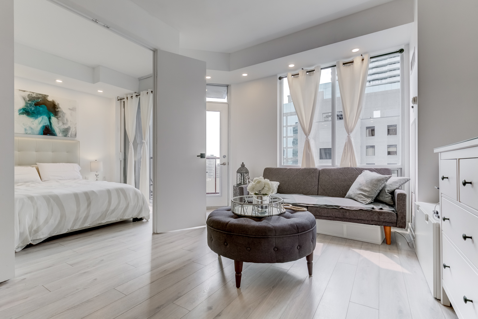 Open-concept design of 85 Bloor Unit 1814 with living room and open bedroom doors.