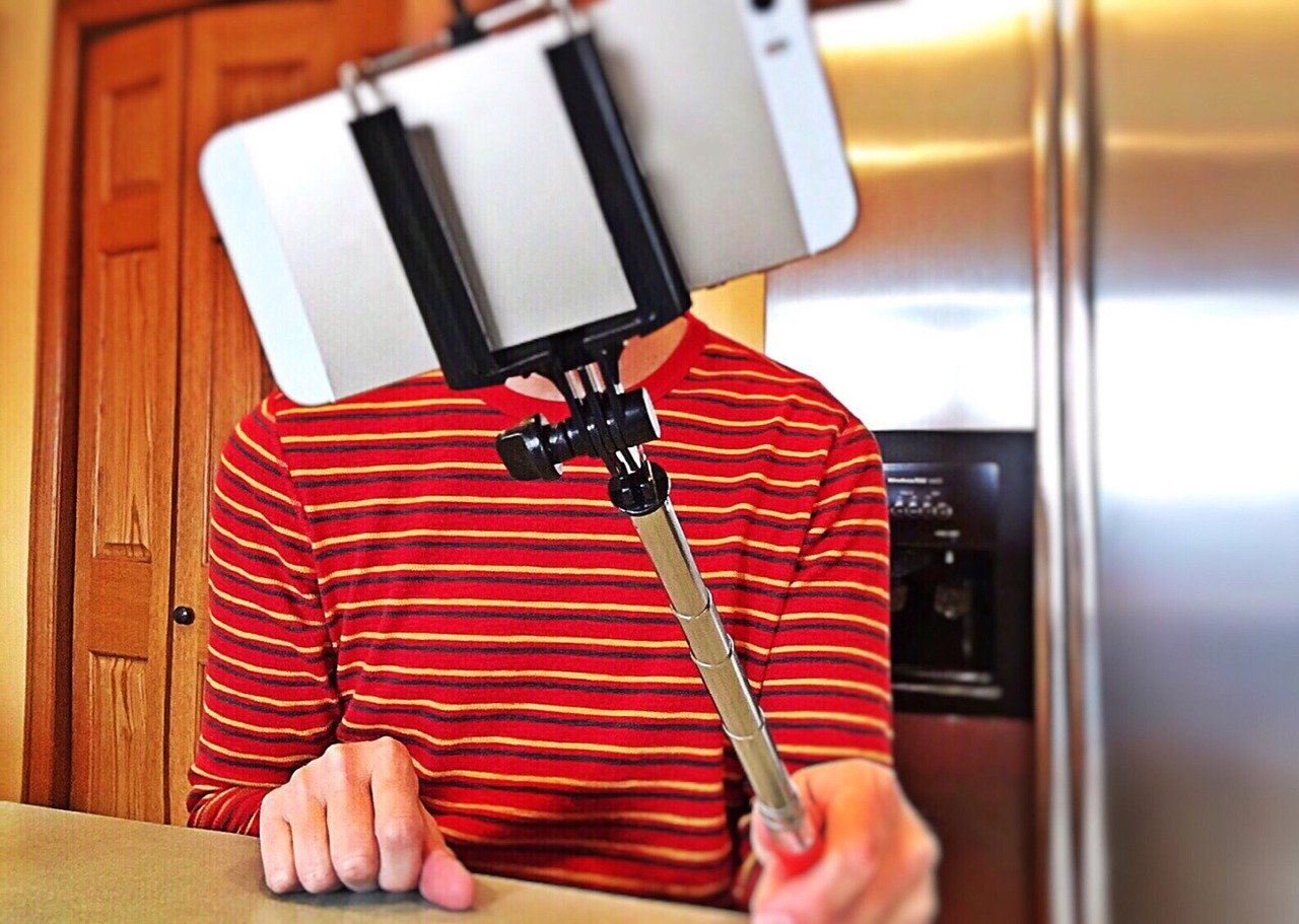 Man in house holding selfie stick with phone.