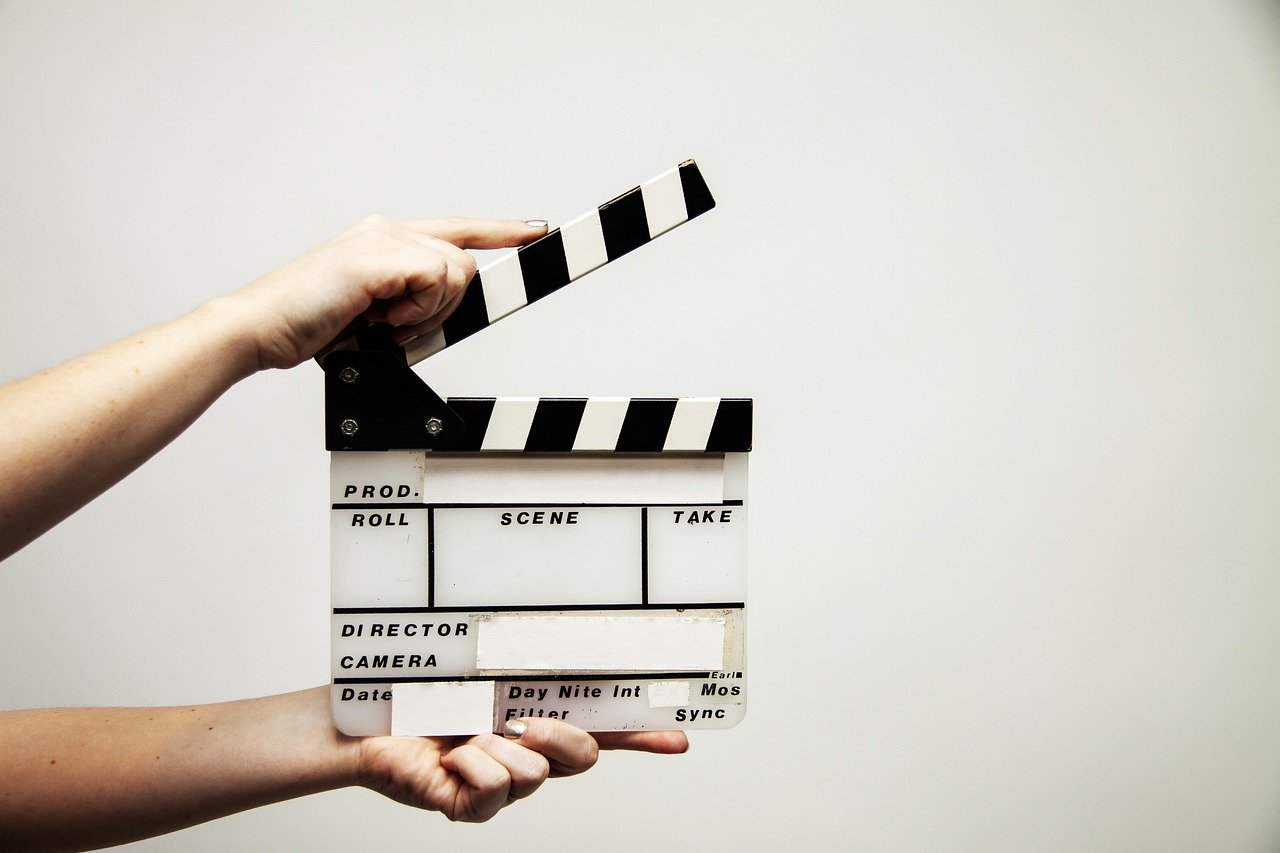 Handing holding clapperboard showing video marketing during COVID-19.