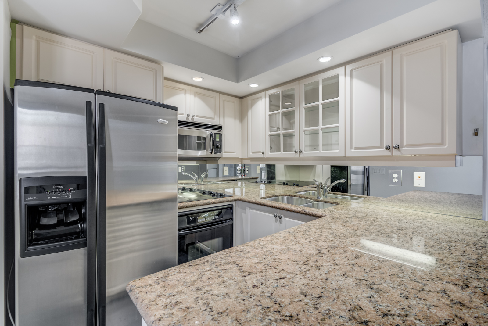 Close up of kitchen granite counter tops and silver appliances.
