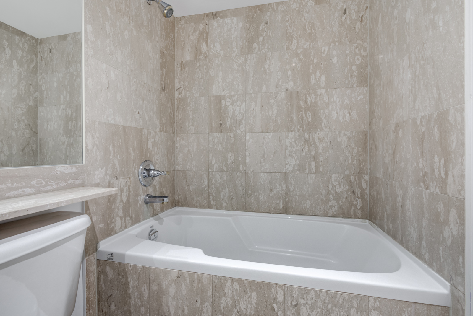 Closeup of 140 Simcoe St E Unit 921 soaker tub with tiles and white trim.