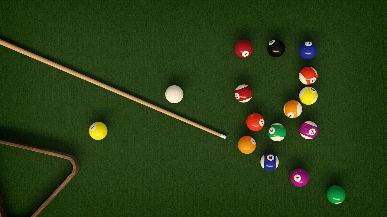 Top down view of billiards table with balls and cue.