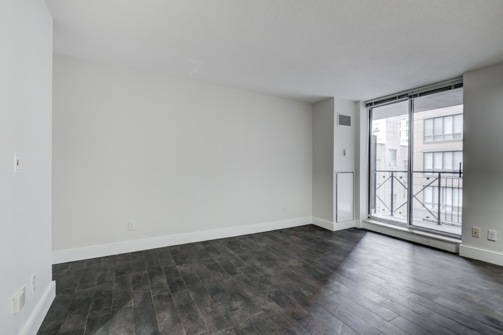 Empty condo with view of balcony and light.