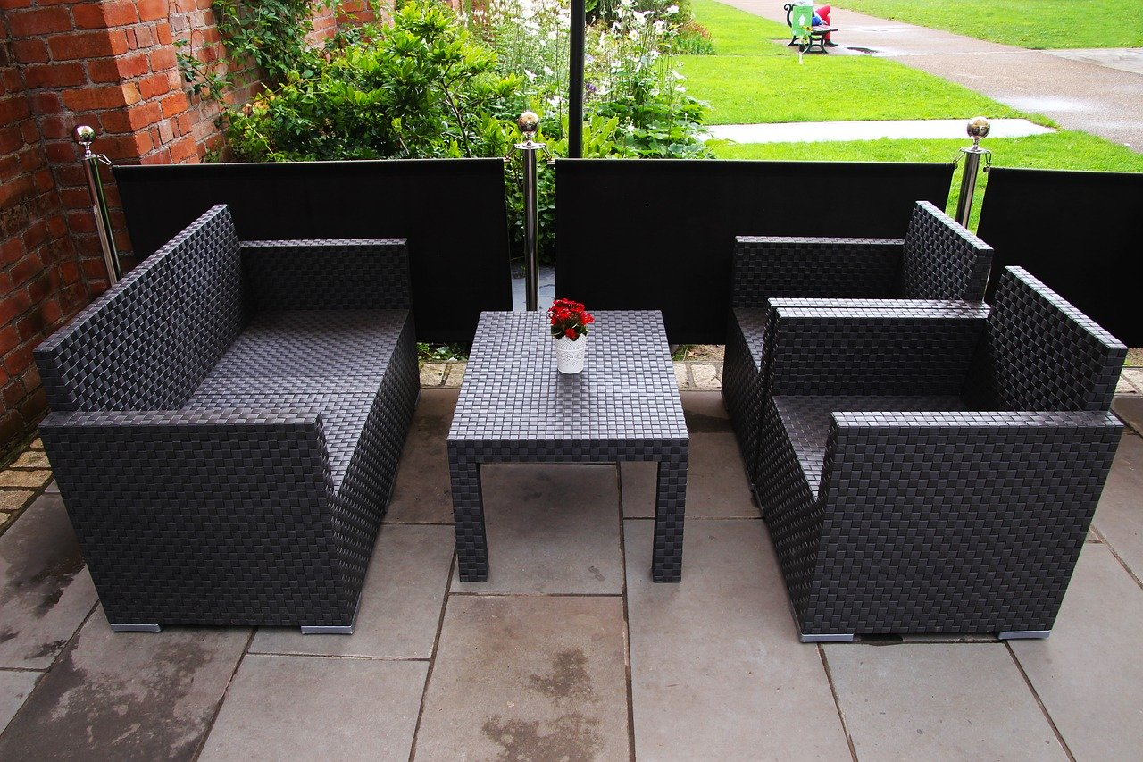 Outdoor patio with 2 black chairs and black table.