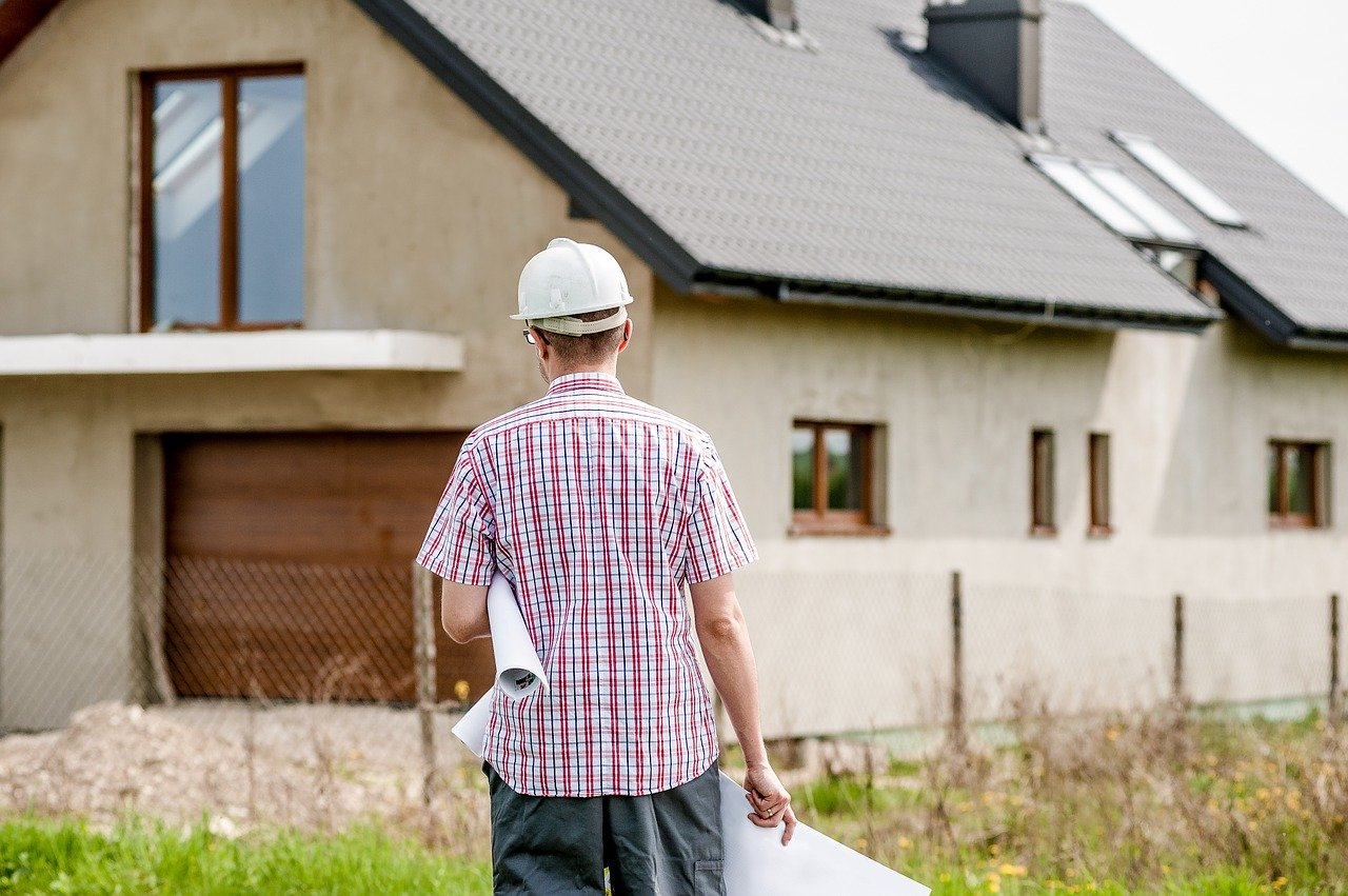 Architect with plans standing in front of house.