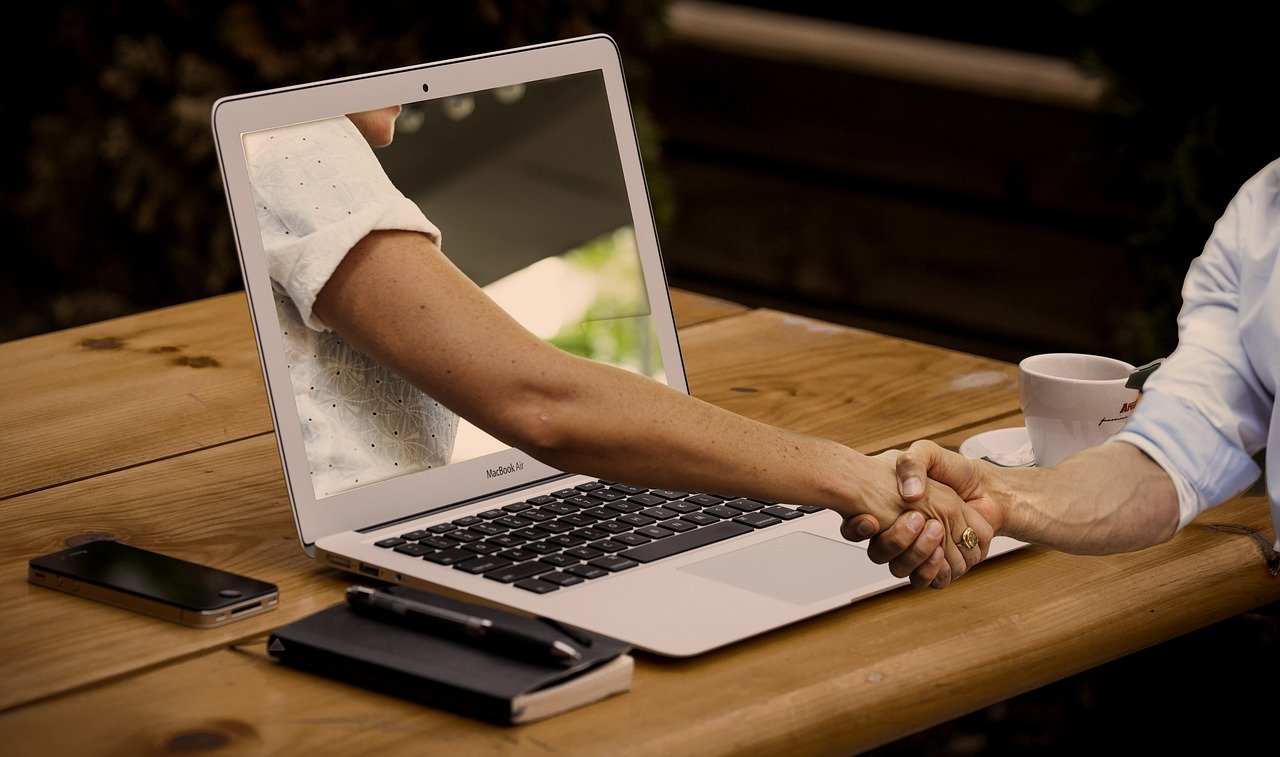 Laptop with hand coming out to shake hands with ask an expert.