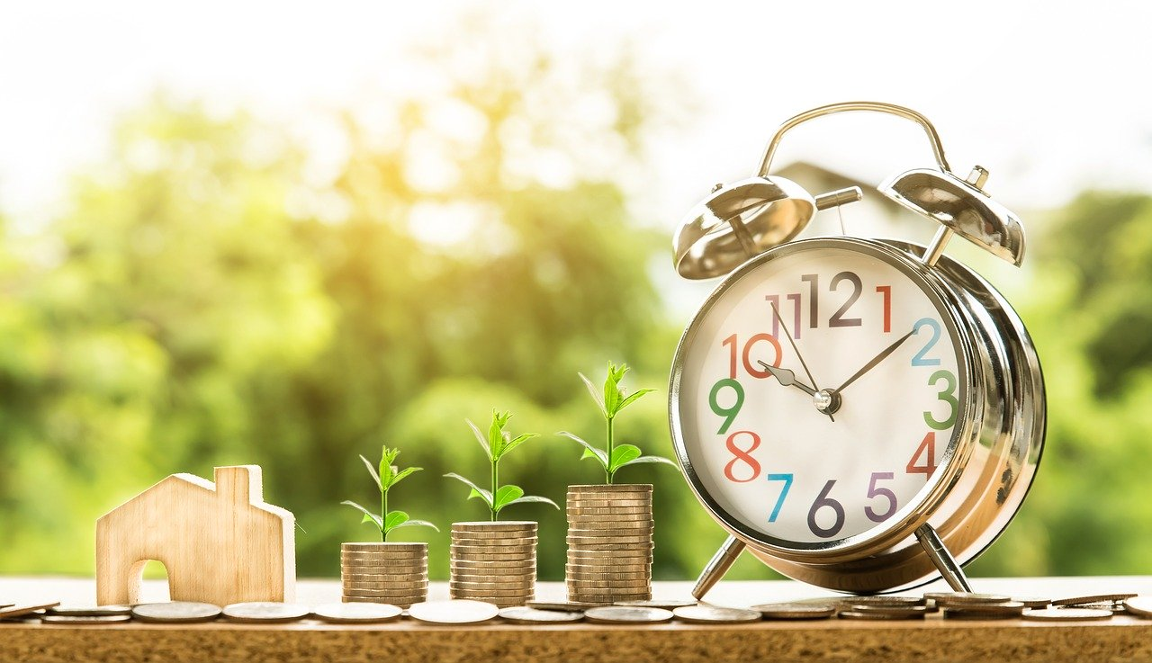 Wooden house, stacked coins and clock to show ask an expert about mortgages.
