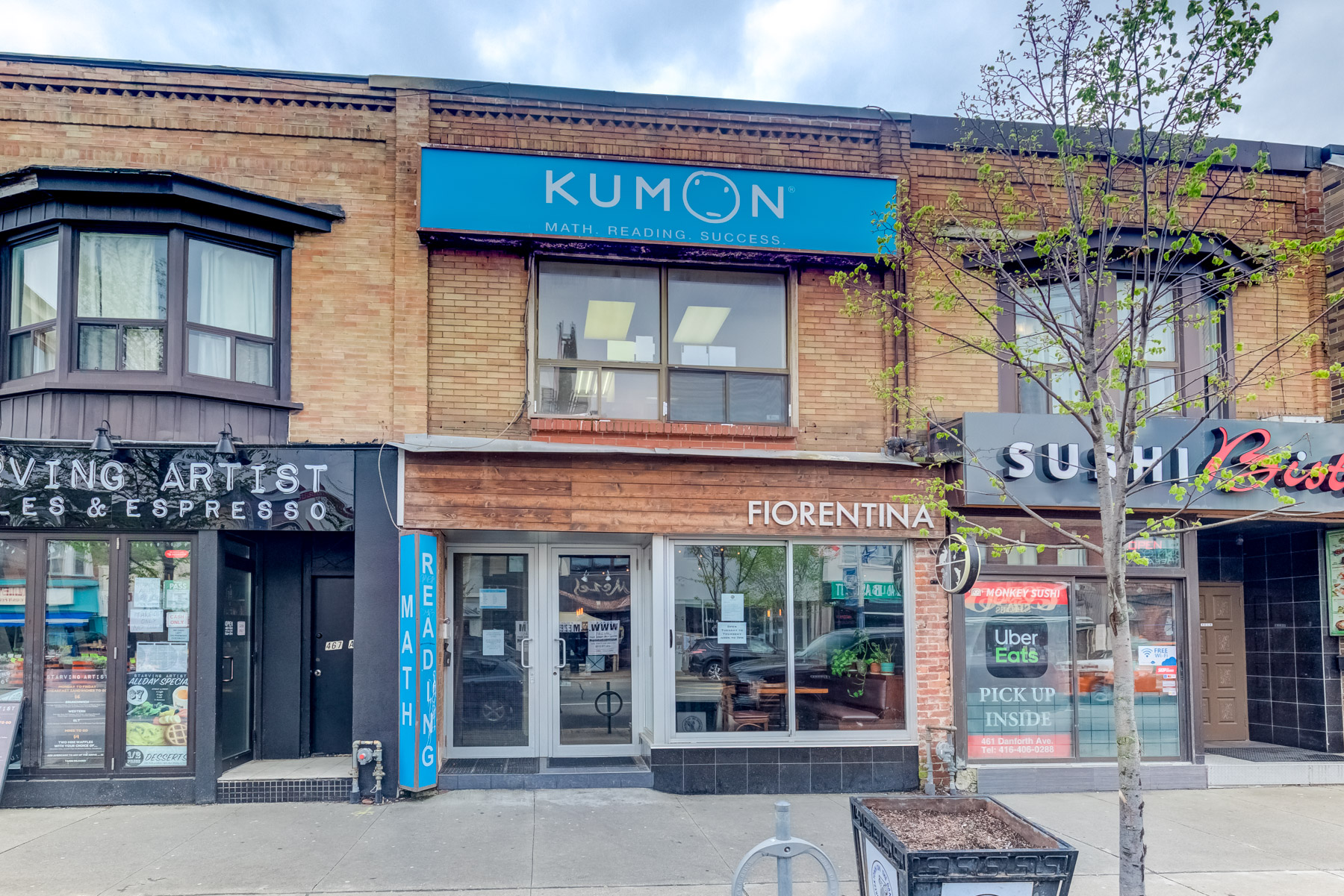Brown brick and wood exterior of 463 Danforth Ave in Toronto.