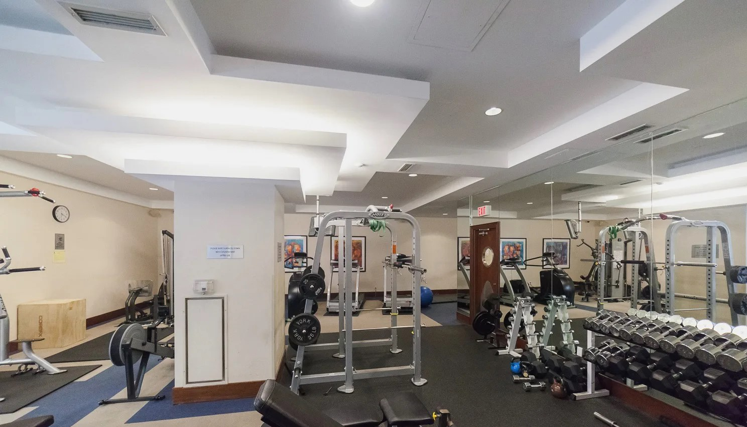 Qwest Condos gym with weights, dumbbells and other exercise equipment.